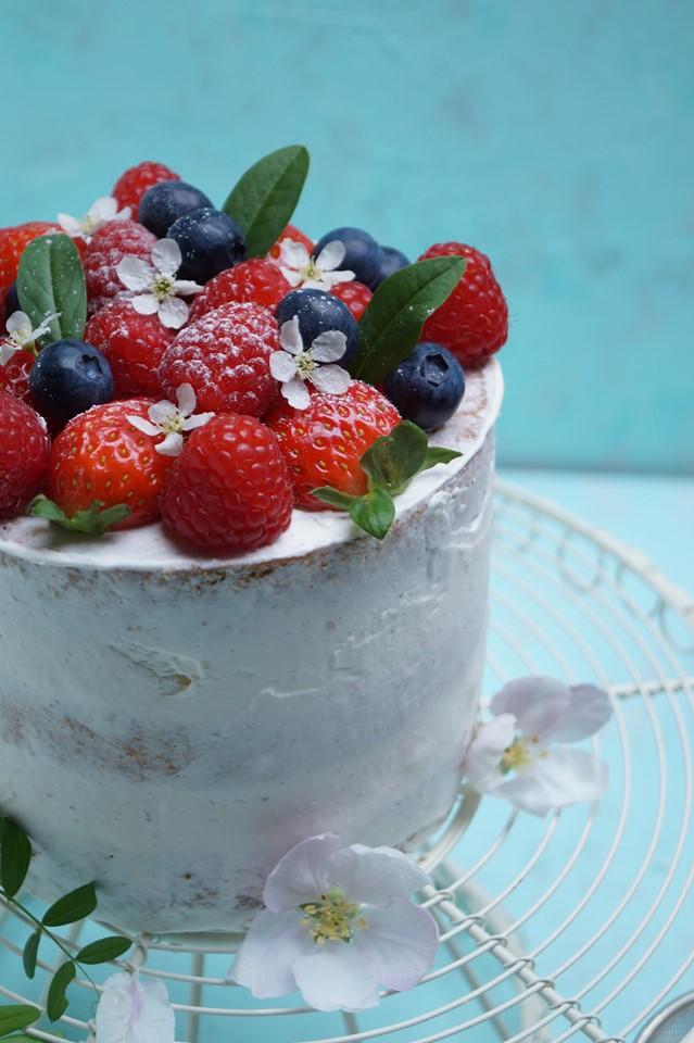 fotografia kulinarna tort z kremem chantilly ze świeżymi owocami maliny, truskawki, borówki zbliżenie na tort